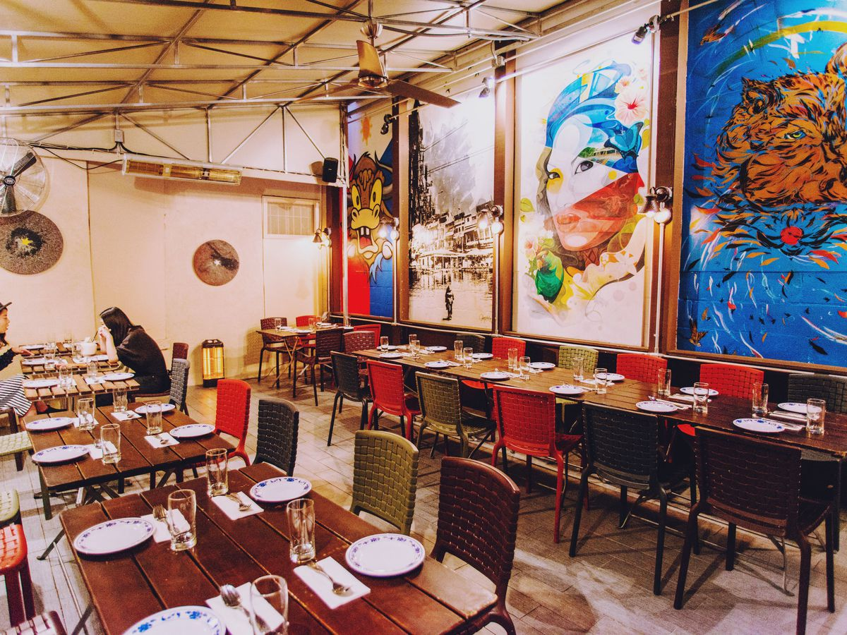 A dining room with four colorful murals on the wall and mahogany wood tables