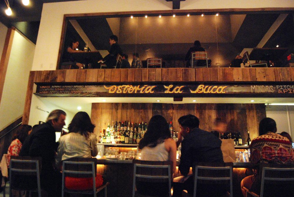 Inside Osteria la Buca, a mellow Italian restaurant in Los Angeles, at night as customers sit at the bar.