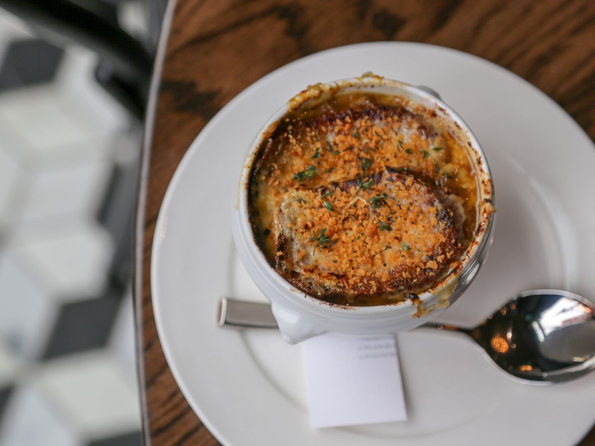 Crock of French onion soup with a spoon