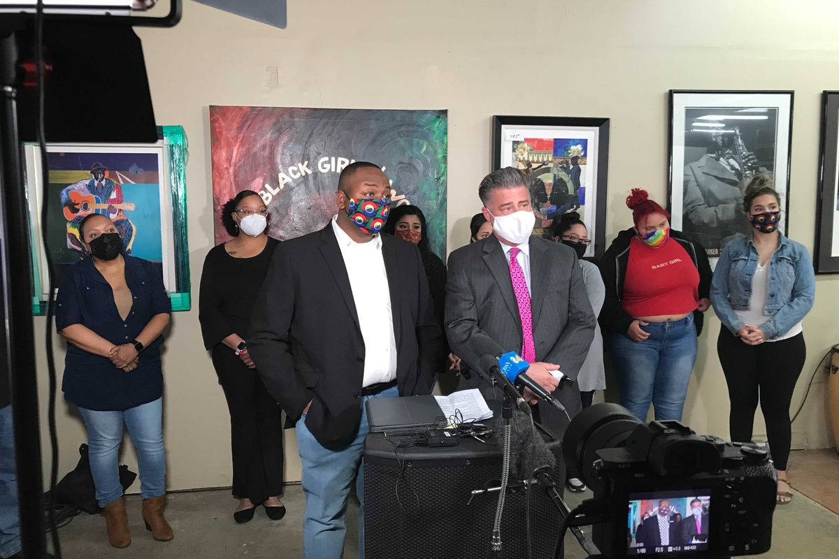 Denver school board member Tay Anderson, left, and his attorney Christopher Decker stand at a podium at a news conference. Supporters stand behind them.