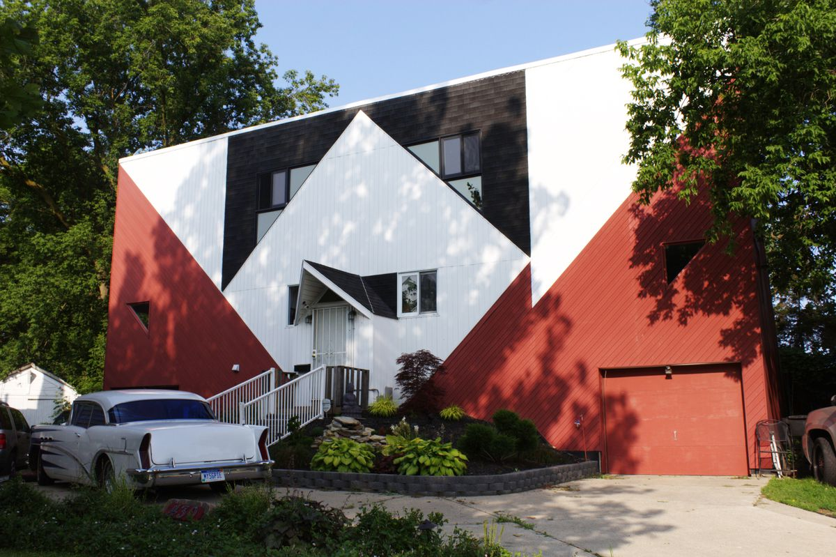 Facade of a white and red house with geometrical squares.