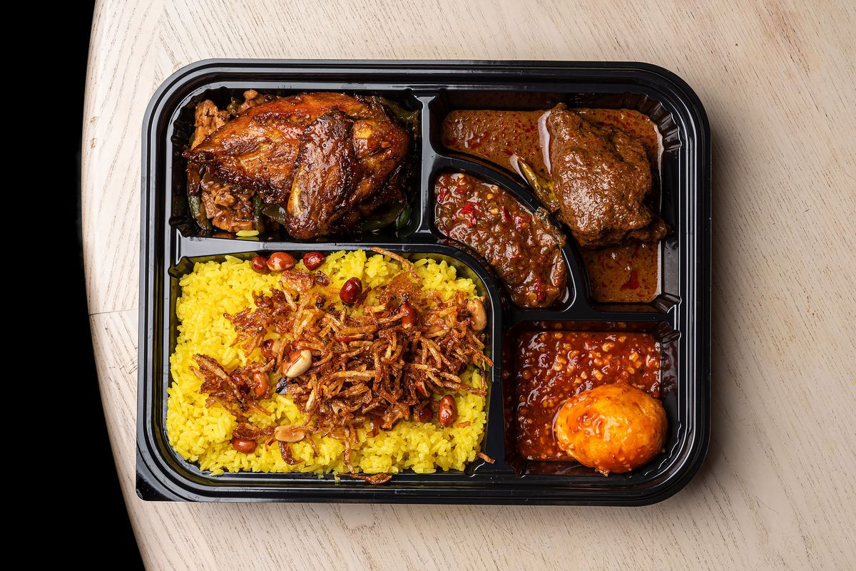 A black tray filled with Indonesian dishes and turmeric rice.
