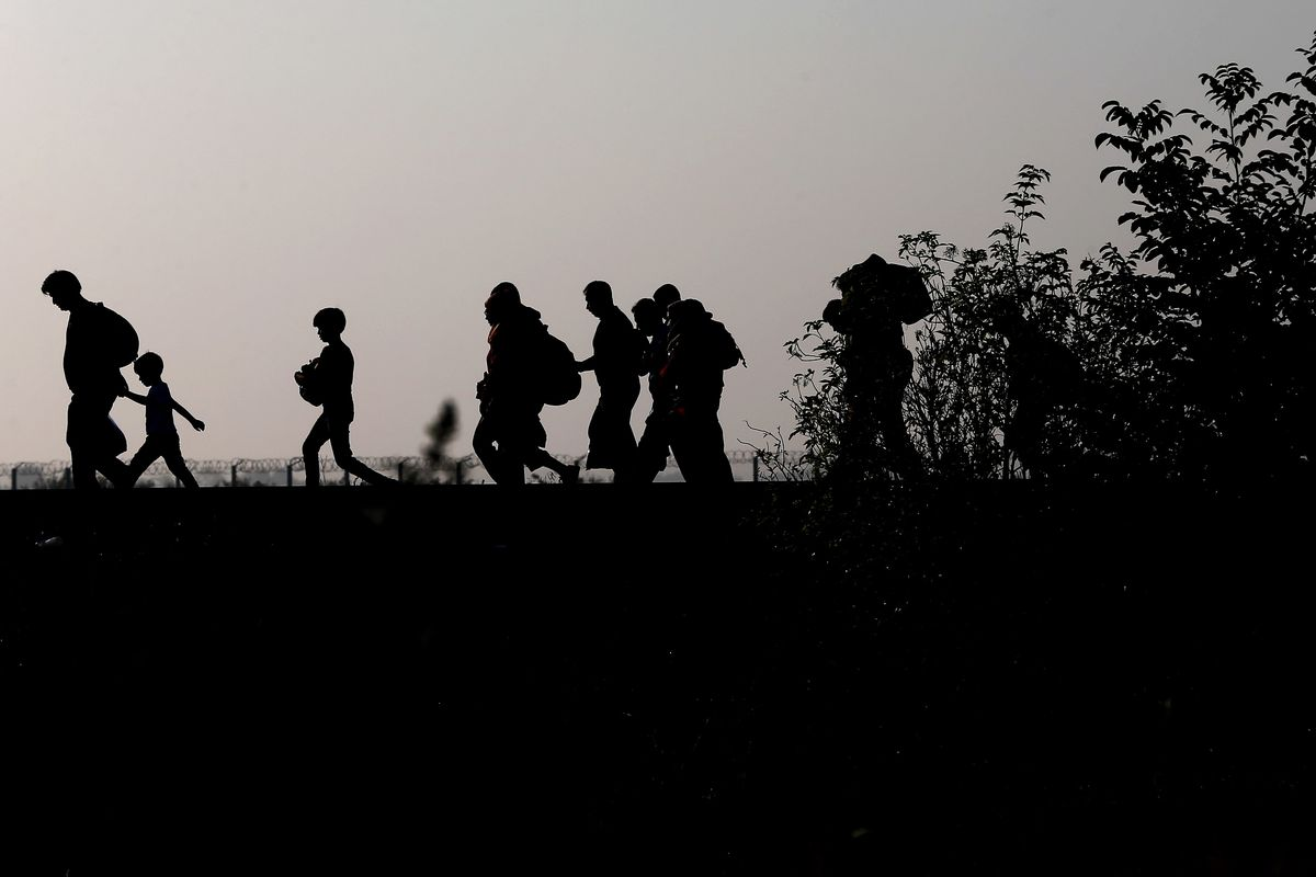 Migrants walk on the railway track after crossing the border line between Serbia and Hungary.
