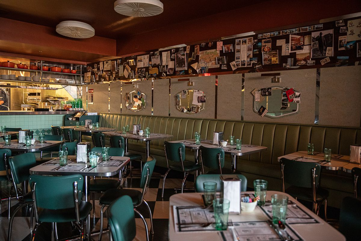 Pale antique green upholstered booths line the walls next to the kitchen at Karl's. The walls feature vintage light fixtures, beige linoleum, and dark wood peg board covered in family photos and momentos.