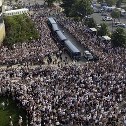 Penn State football fans surround the Penn State football team as they arrive by bus at Beaver Stadium for their season opener NCAA college football game against Ohio in State College, Pa., Saturday, Sept. 1, 2012.