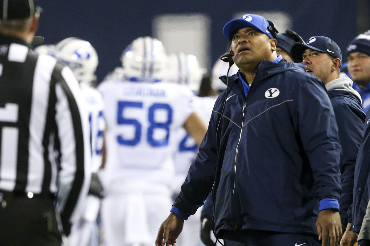 BYU coach Kalani Sitake watches a replay that overturned a fumble recovery by BYU against Utah State at Maverik Stadium.