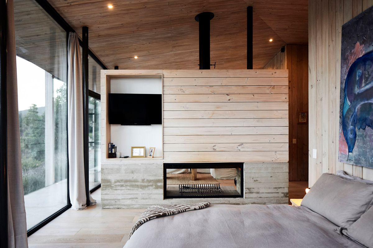 A bedroom is separated from the living room wood-plank wall with a recessed area for TV and decor. Curtains flank glass walls looking to the outdoors.