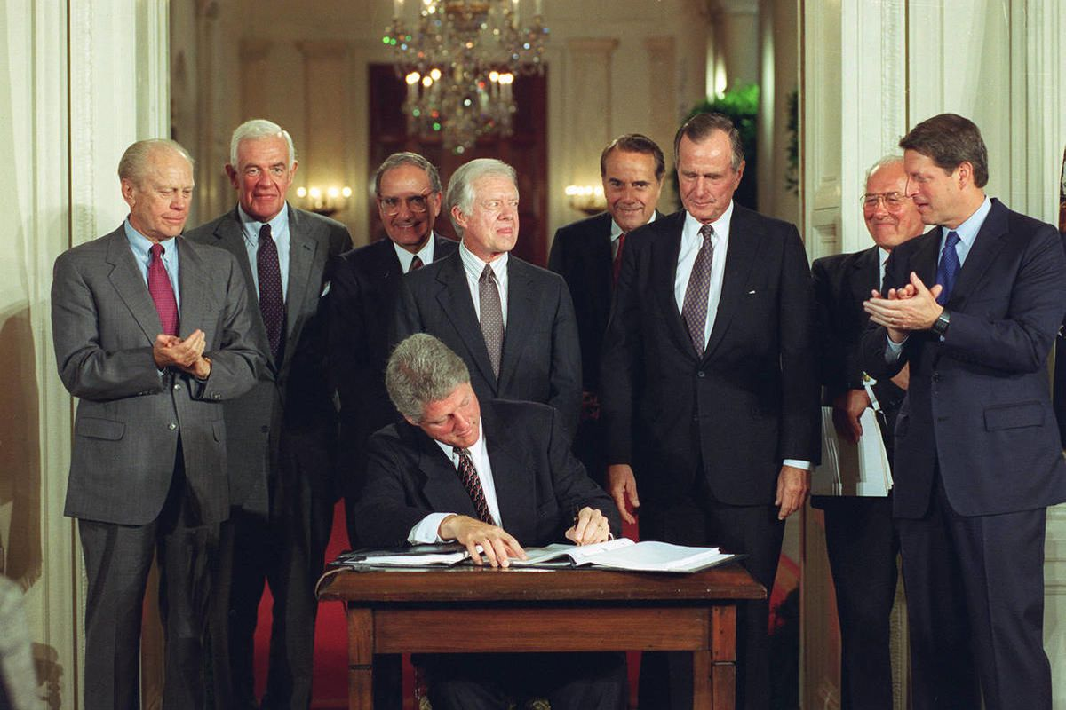 U.S. President Bill Clinton signs side deal of the three-nation North American Free Trade Agreement (NAFTA) at the White House, Washington, D.C., Tuesday, Sept. 14, 1993.  Joining President Clinton are, from left, fomer President Gerald Ford, House Speake