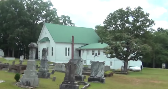 In the foreground is a lawn with various tombstones on it. In the distance is a church with white walls and a green roof.