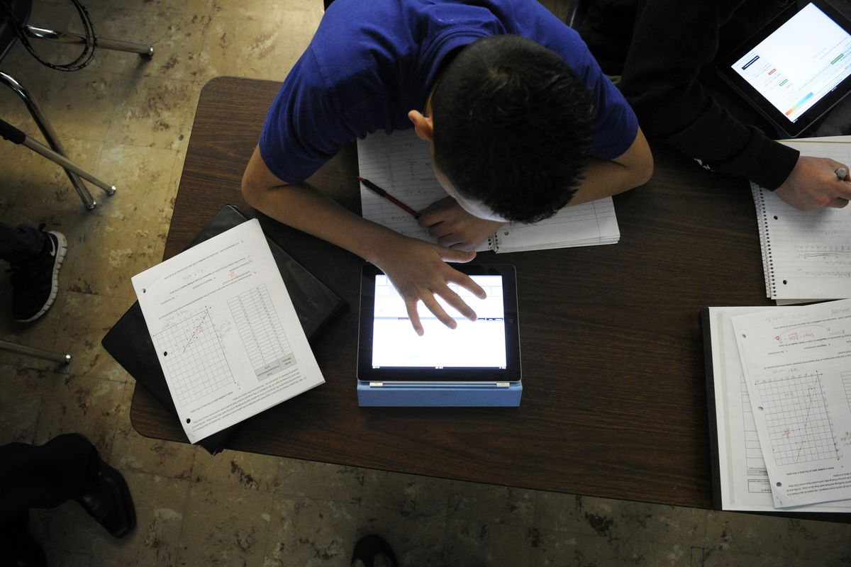 Grant Beacon Middle School student Jeriah Garcia works out an algebra problem on his school-supplied tablet in 2012.