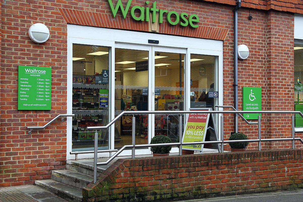 Exterior shot of brick facade of grocery store with Waitrose in green lettering above sliding glass doors up a couple of steps.