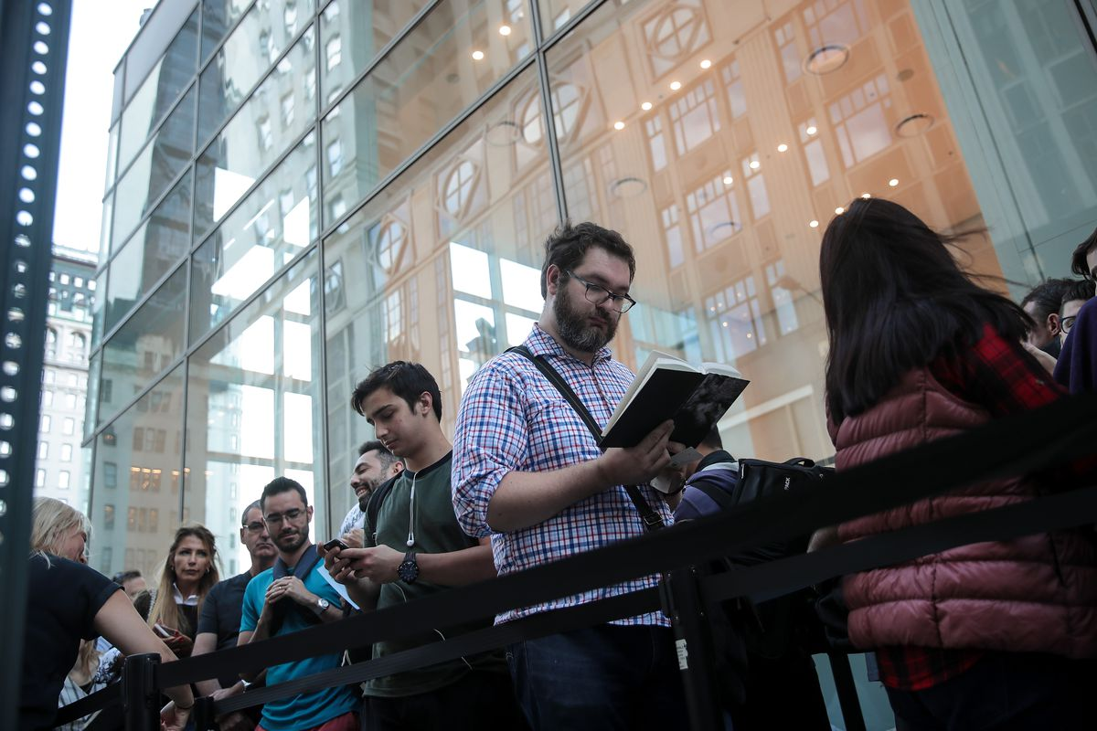 People stand outside an Apple store looking at books and phones.