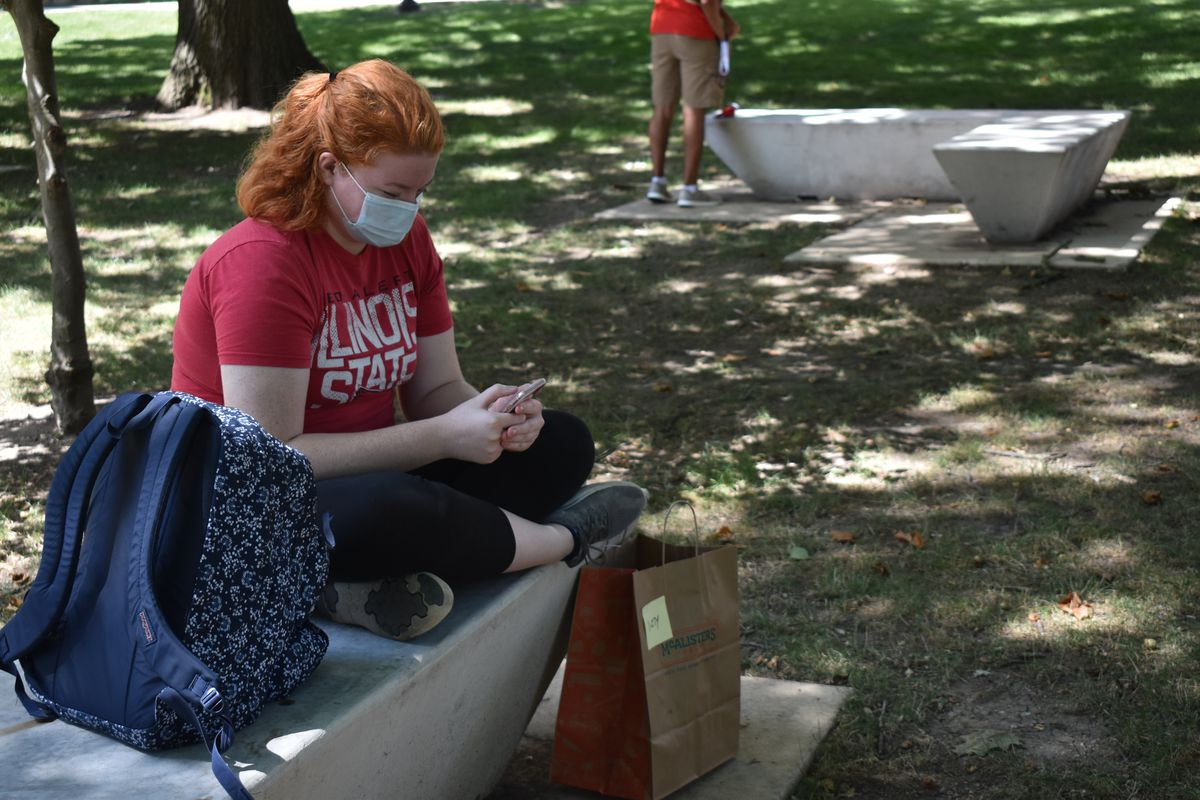 Illinois State senior Lizzie O'Dwyer sits on the university's quad on Monday. She had already attended two in-person classes on the first day.