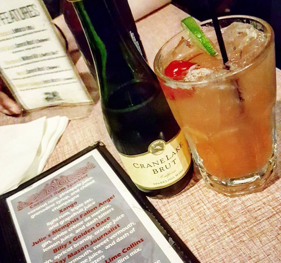 A plastic-covered cocktail menu, a small bottle of Crane Lake Brut, and a pint glass filled with a pink cocktail sit on a table.