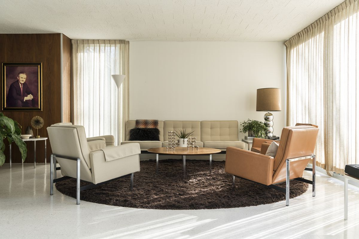The living room of the house is white with accent walls of wood veneer. Midcentery Modern furniture (leather Knoll chairs, a sofa, and a coffee table) furnish the room.