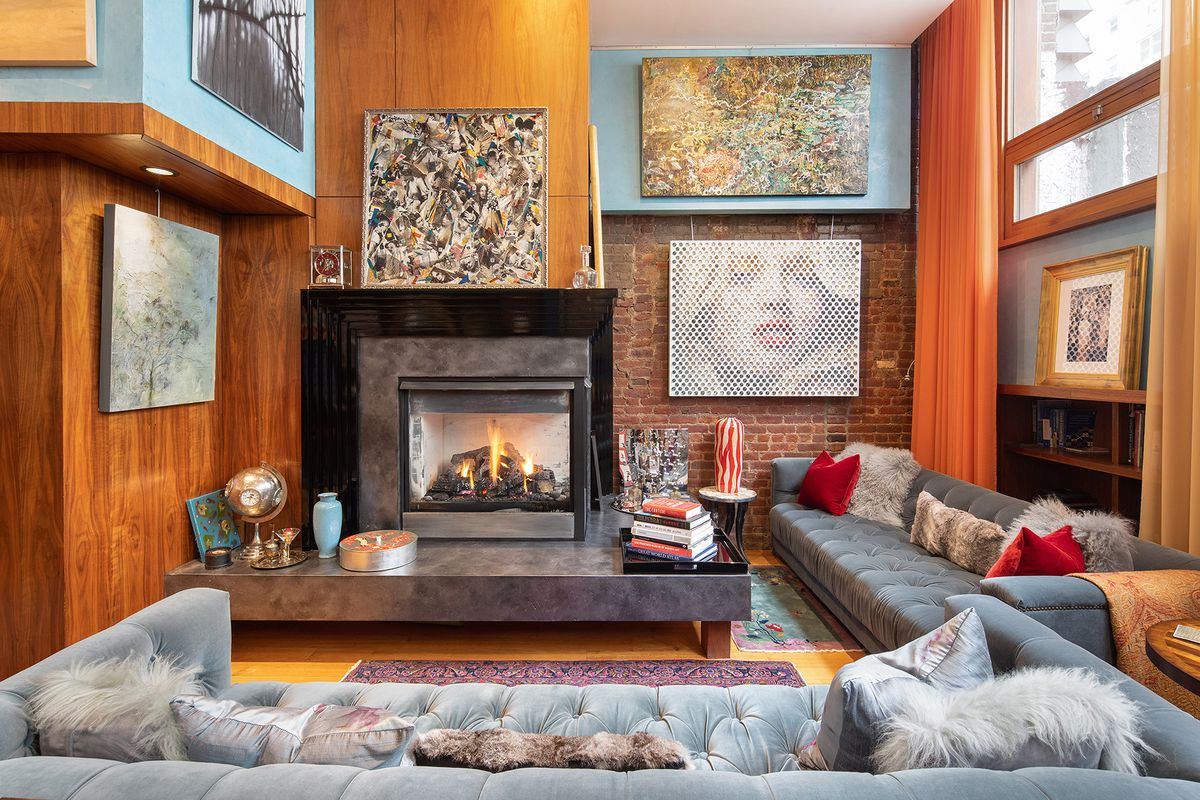 A living room with a gas fireplace, exposed bricks, several paintings hanging on the wall, and several light grey couches.
