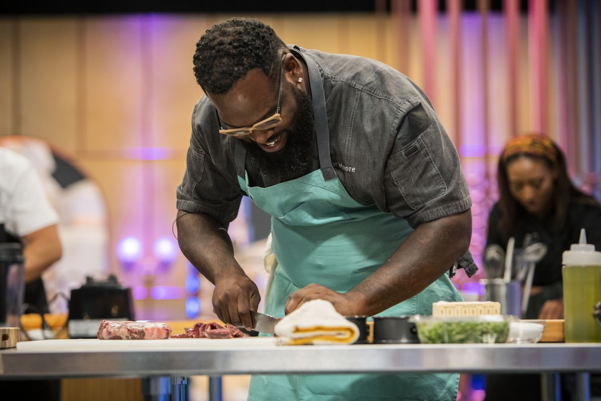 A chef holding a knife while competing on Food Network.