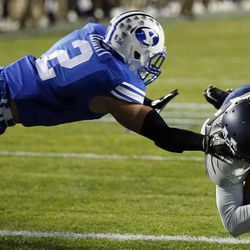 Darell Garretson (10) of the Utah State Aggies dives in for a touchdown while defended by Dallin Leavitt (2) of the Brigham Young University Cougars during NCAA football in Provo, Friday, Oct. 3, 2014.