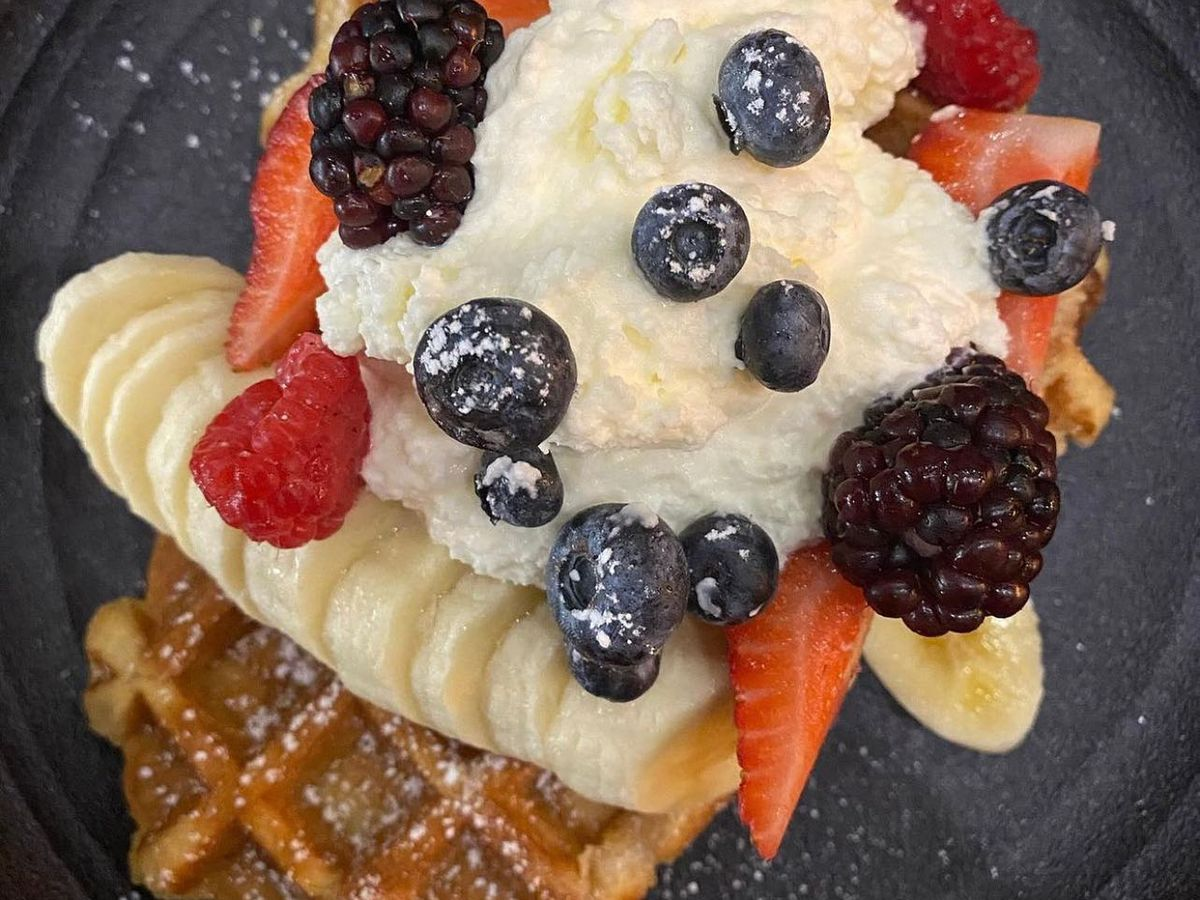 Waffle topped with berries and whipped cream.