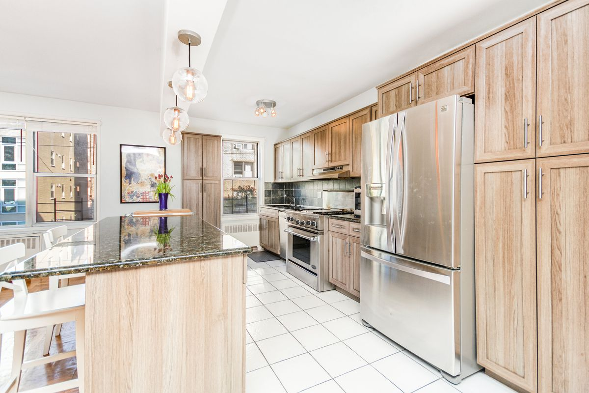 A kitchen with white floor tiles and wood cabinetry.