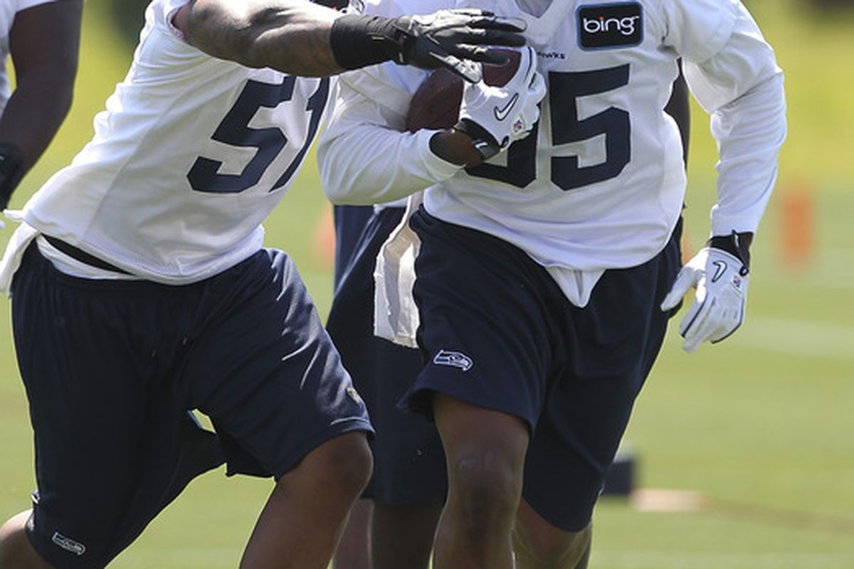 RENTON, WA - MAY 11:  Defensive end Bruce Irvin #51 of the Seattle Seahawks strips the ball from Pierre Allen #95 during minicamp at the Virginia Mason Athletic Center on May 11, 2012 in Renton, Washington. (Photo by Otto Greule Jr/Getty Images)