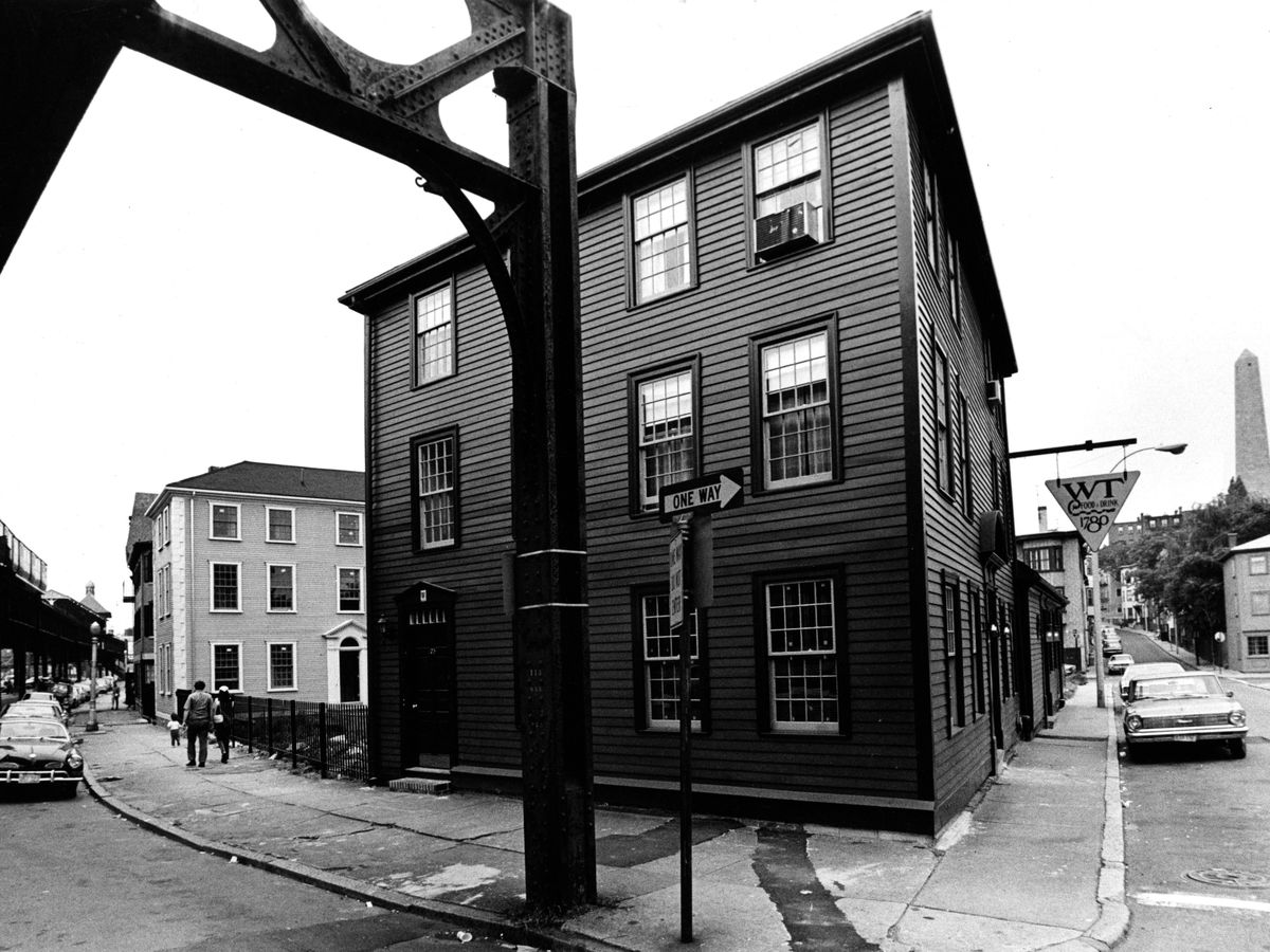 A three-story, square building on a street corner.