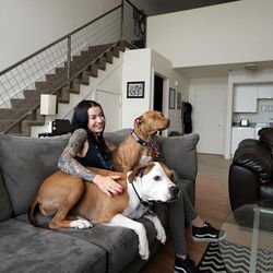 Kenzie Smith sits with her dog, Buddha, and her boyfriend's dog, Harley, at her apartment in Salt Lake City on Thursday, April 28, 2016.