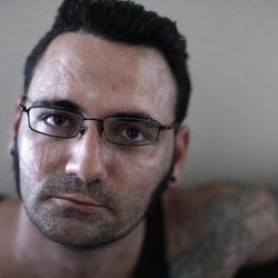 """This Tuesday, Aug. 2, 2011 photo shows former skinhead Bryon Widner at his home. For 16 years, Widner was a glowering, strutting, menacing vessel of hate - an """"enforcer"""" for some of America's most notorious skinhead groups."""