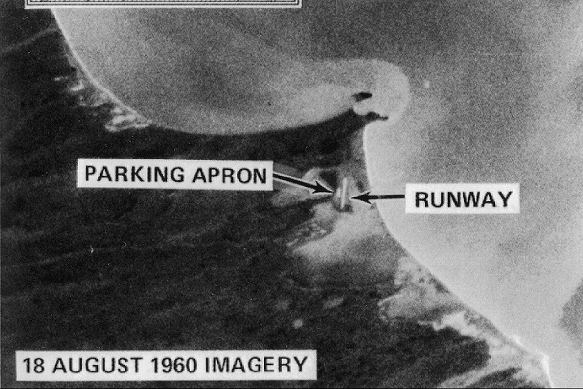 """A black and white satellite photo of an area in Russia, with text that says """"18 August 1960 Imagery."""" There are arrows pointing to areas that say """"Parking Apron"""" and """"Runway."""""""