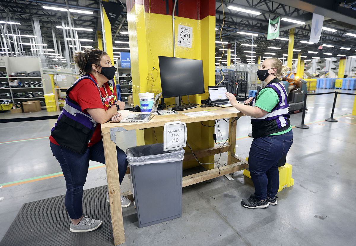 Victoria Le, Amazon assistant general manager, talks with Megan Jones, Amazon operations manager, at the Amazon Fulfillment Center in Salt Lake City on Friday, May 7, 2021.