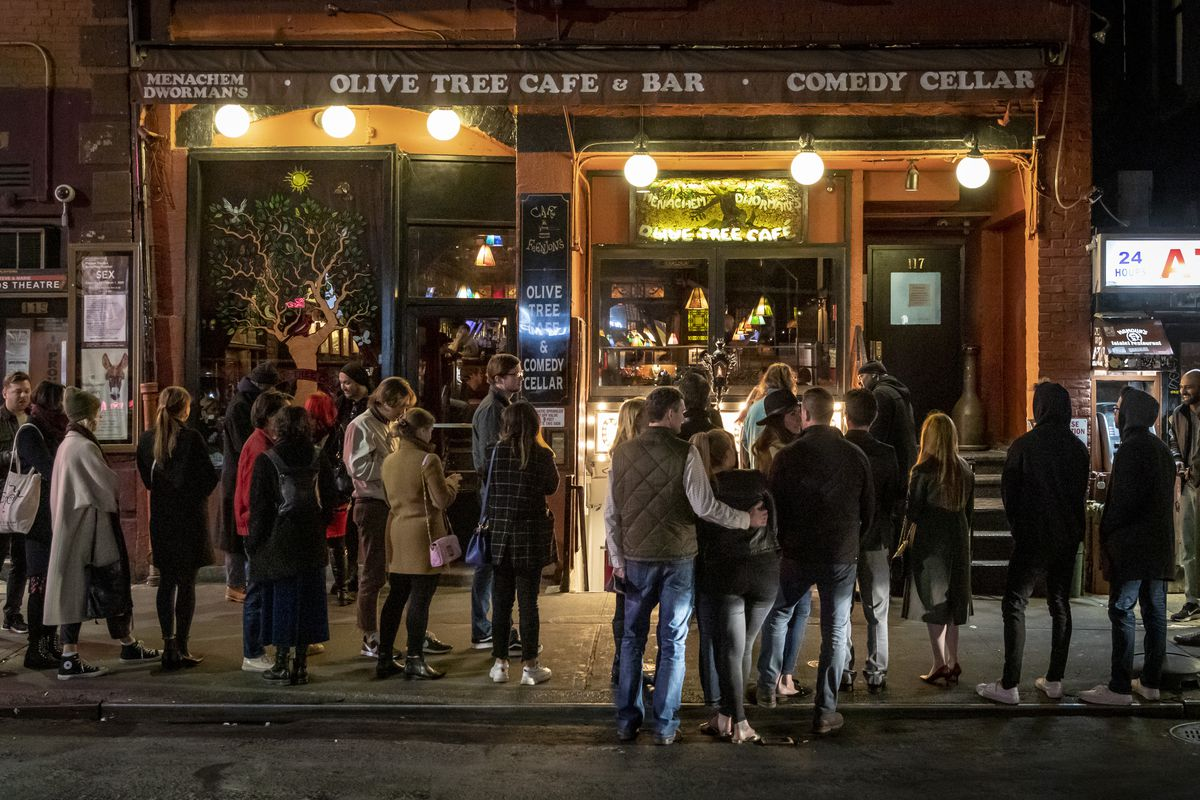 A group of people stand huddled outside of a restaurant at night