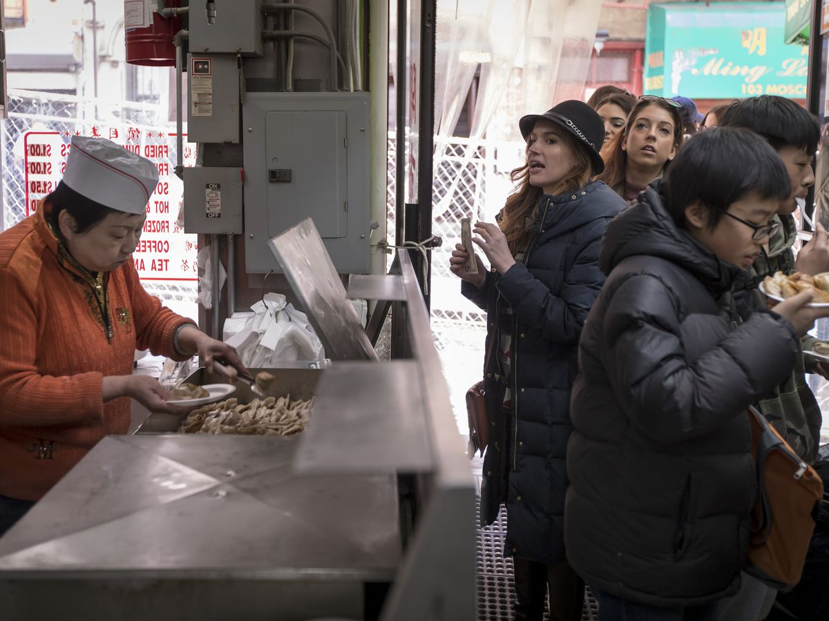 A woman in a red jacket with a white paper hat serves dumplings to a line of customers