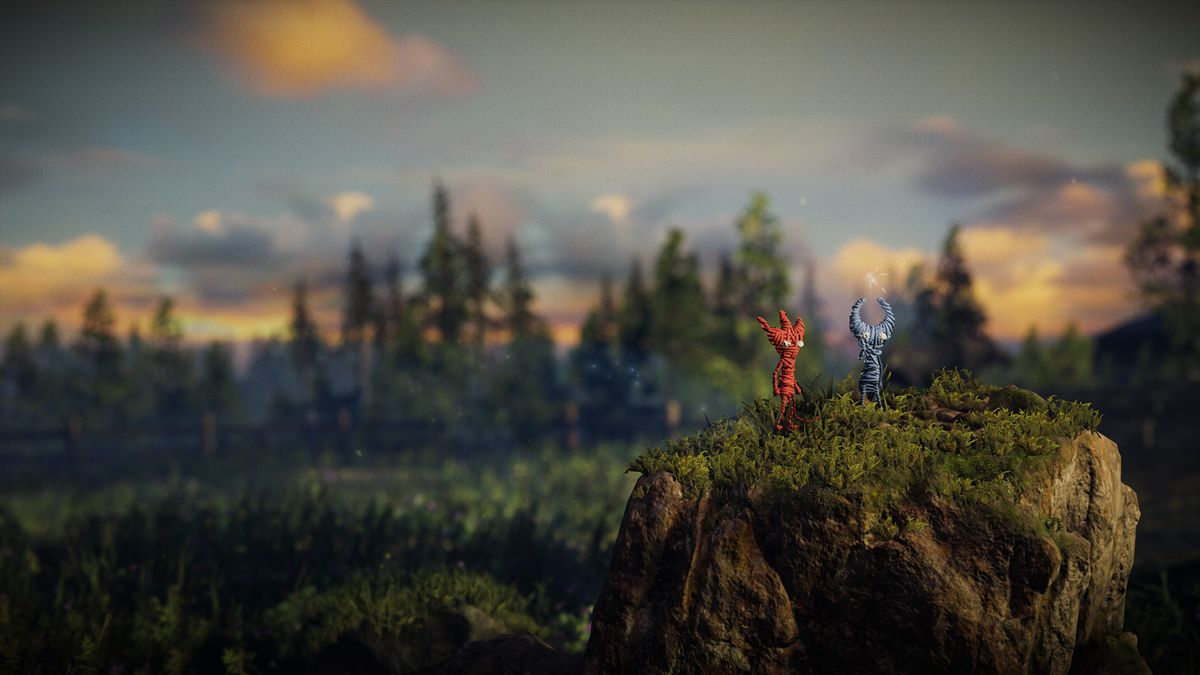 Unravel 2 - two Yarnys standing on a rock at golden hour