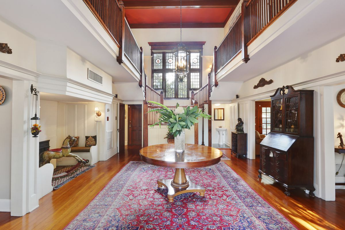 A grand entry with two-story ceilings and wood floors and a wooden staircase at the rear behind a small table