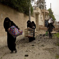 Iraqi women flee heavy fighting in the Yarmouk district of western Mosul, Iraq, Tuesday, April 11, 2017.