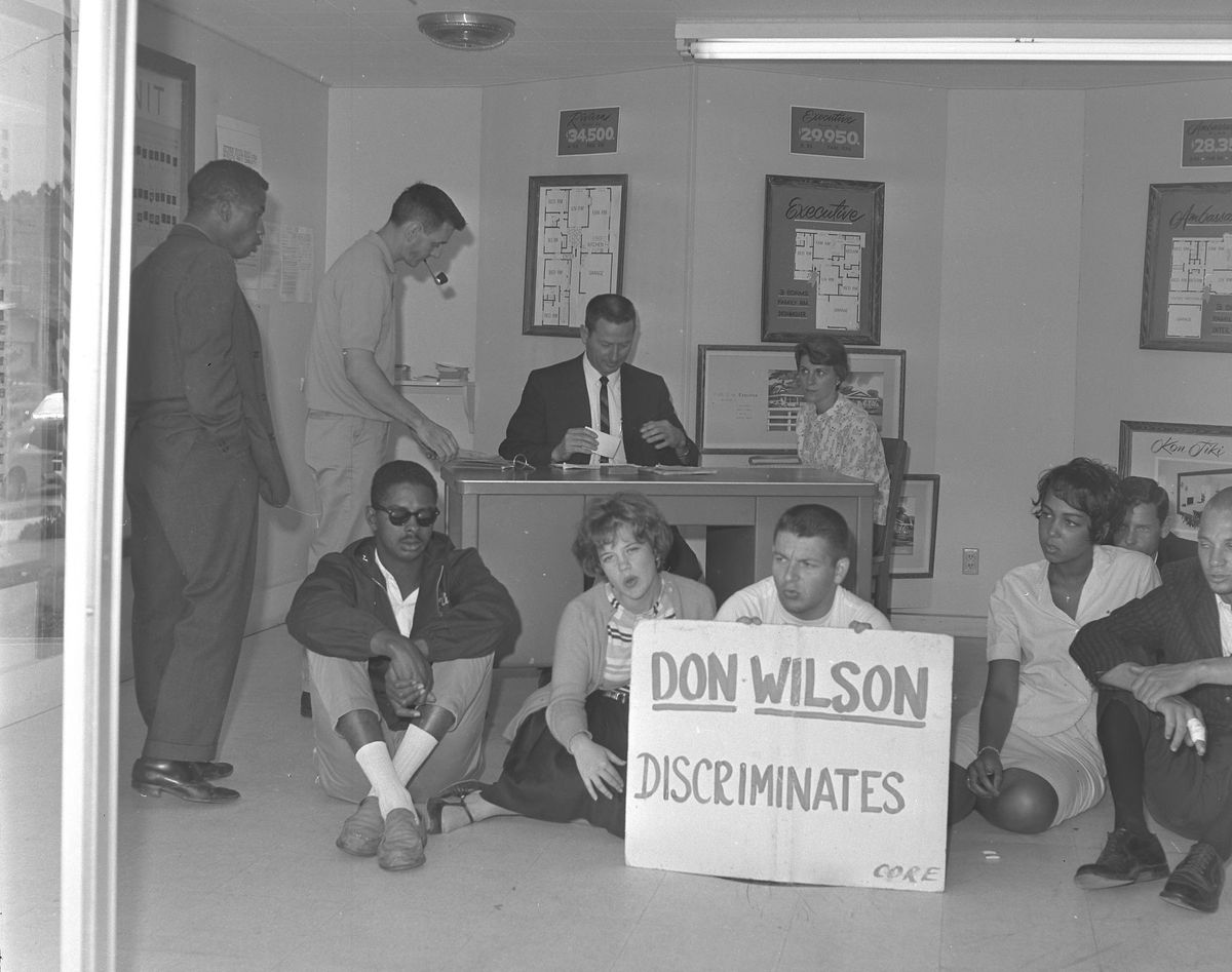 """Young black and white people sit in front of a desk in an office holding a sign that says """"Don Wilson Discriminates."""""""