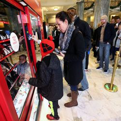Brittany Ryan helps her sons Schroeder and Hudson at the Light the World charity vending machines in the Joseph Smith Memorial Building in Salt Lake City on Friday, Dec. 15, 2017.