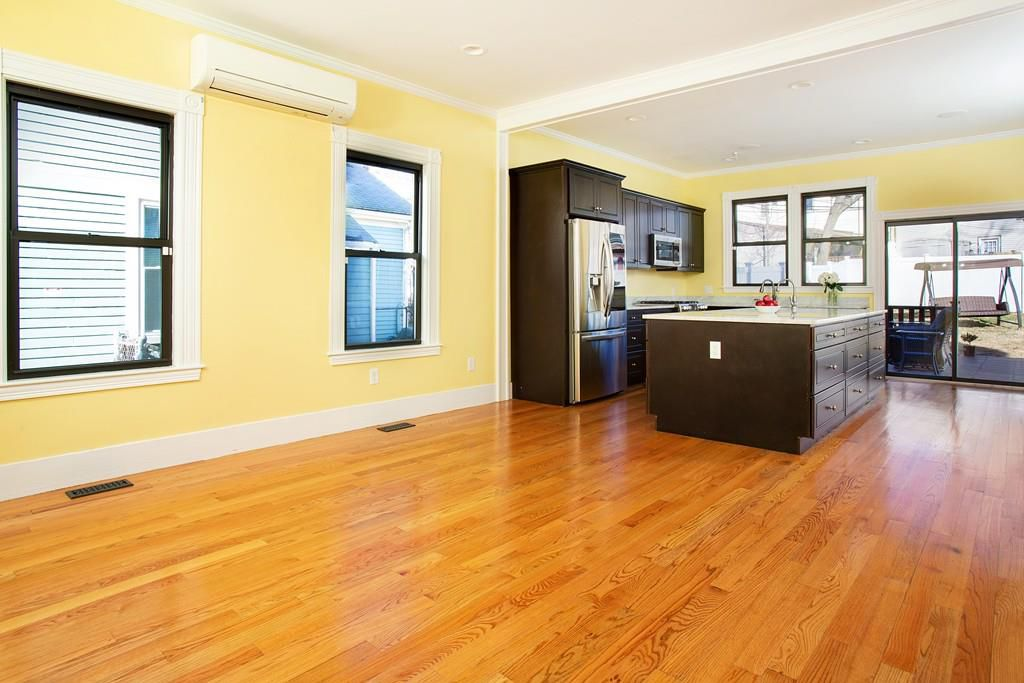A spacious and empty kitchen-living room area with a kitchen island.
