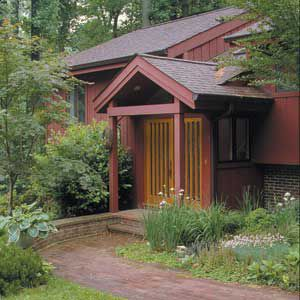 <p><strong>AFTER:</strong> Running Remodeling, of Kensington, Maryland, put in some smart double doors, and sheltered them with a simple front-gable canopy set into the existing roof.</p>