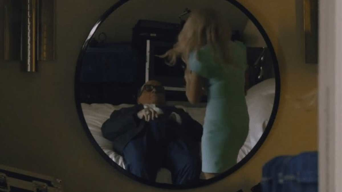 Rudy Giuliani lays on a hotel bed, hand down his pants (allegedly tucking in his shirt), while we see the back of a blonde woman in a tight mint-colored sheath dress.