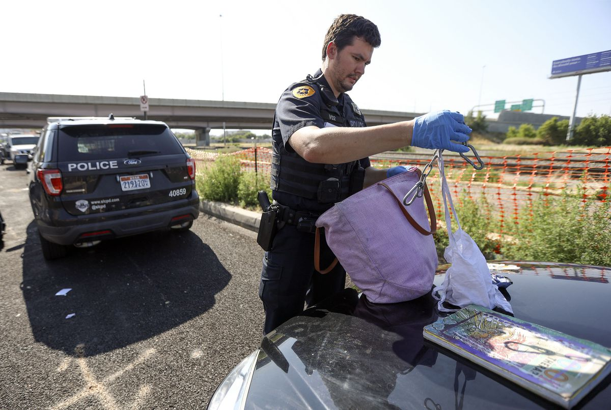 Salt Lake police officer Christopher Berry looks through a woman's bag after she was found trespassing in a stranger's apartment in Salt Lake City on Tuesday, Aug. 3, 2021.