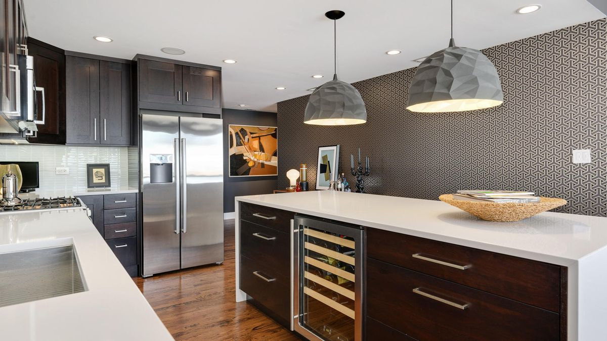 Kitchen with geometric wallpaper and a large island with white stone counters and two angular accent pendant lights.