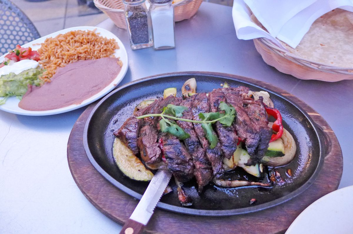 A metal platter with browned and sliced strips of meat, with a plate of refried beans and other toppings in the corner of the picture.
