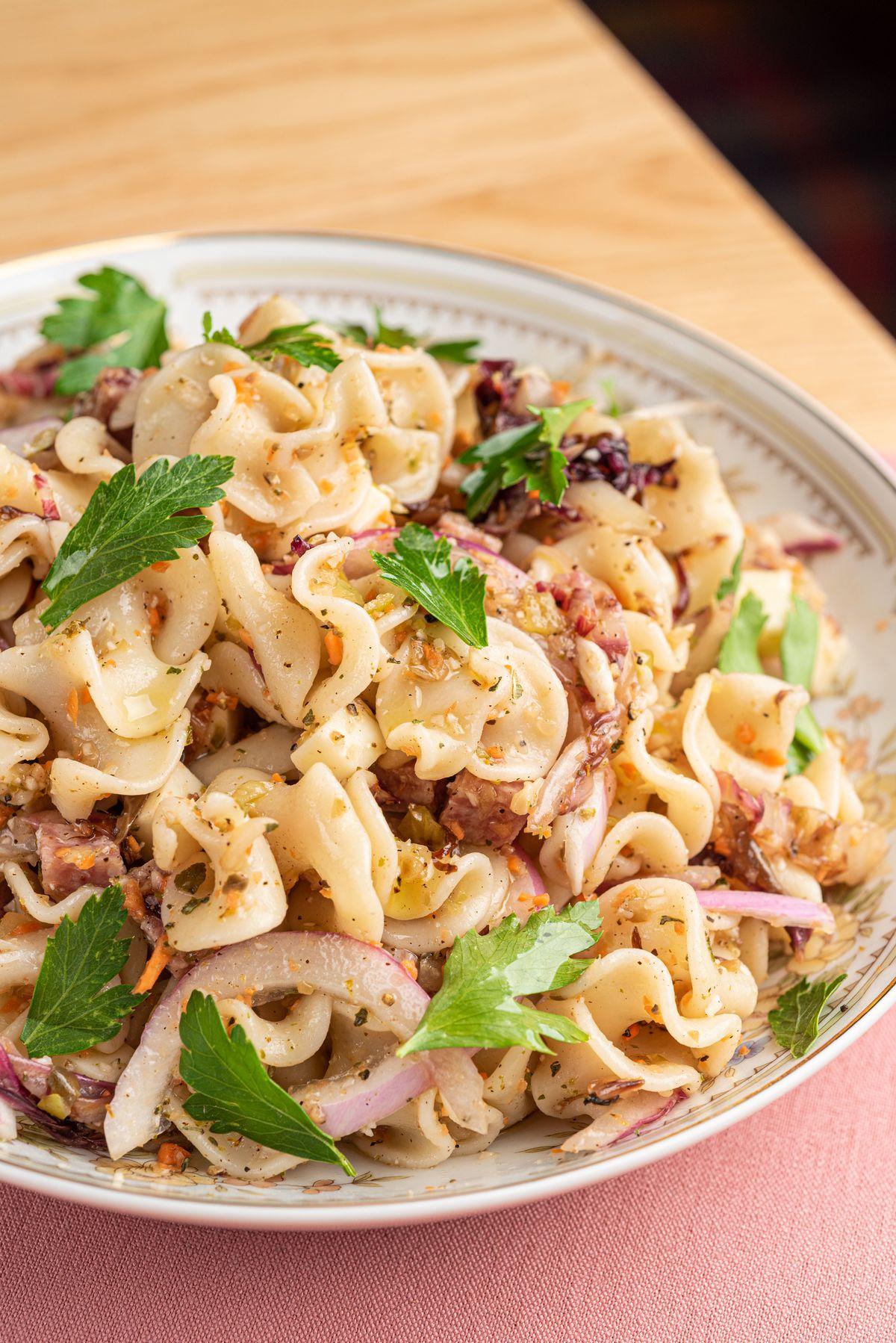 A bowl of pasta with Italian seasonings, onions, and mozzarella.
