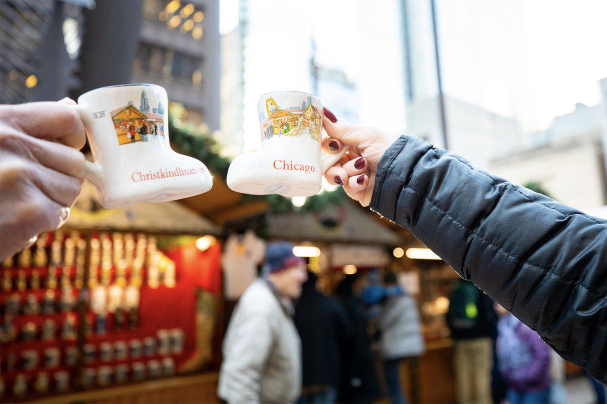 Two people holding small boot-shaped mugs cheers outside a Germanic-looking Christmas market stall.