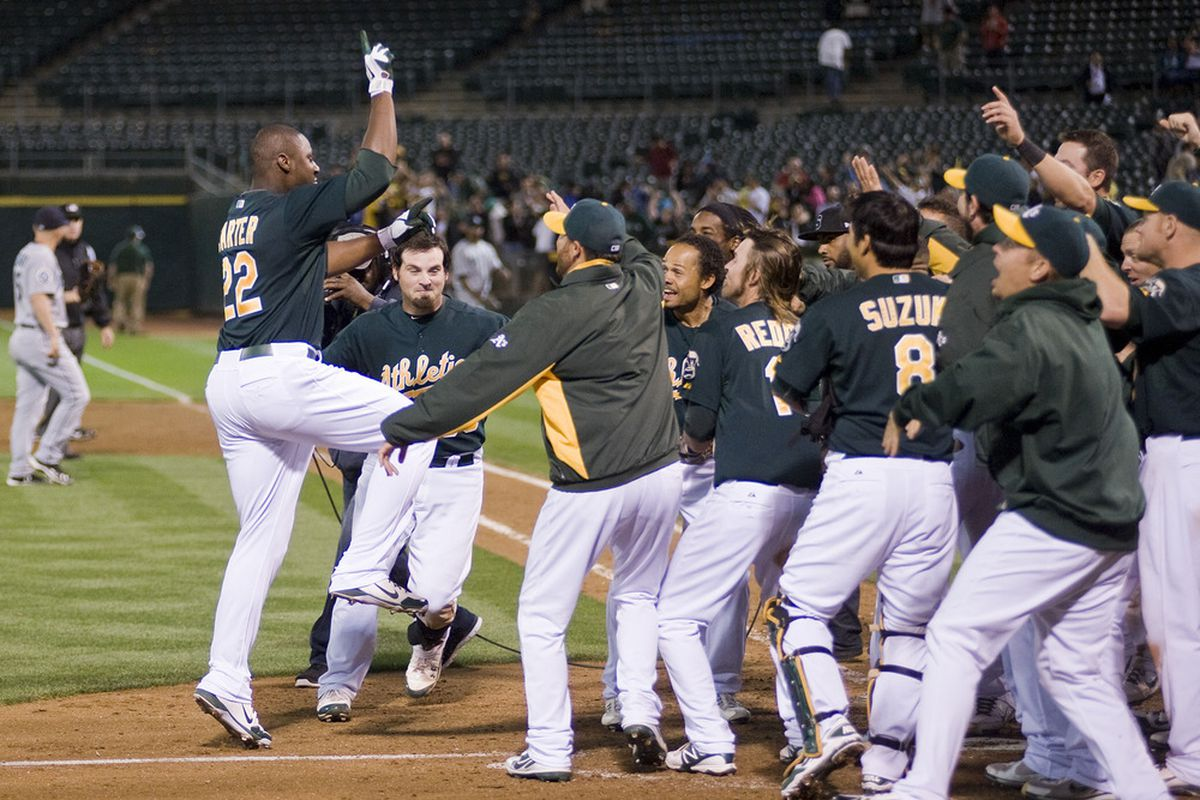 July 6, 2012; Oakland, CA, USA; Oakland Athletics first baseman Chris Carter (22) celebrates with teammates at home plate after hitting a walk off home run to beat the Seattle Mariners at O.co Coliseum.  Mandatory Credit: Ed Szczepanski-US PRESSWIRE