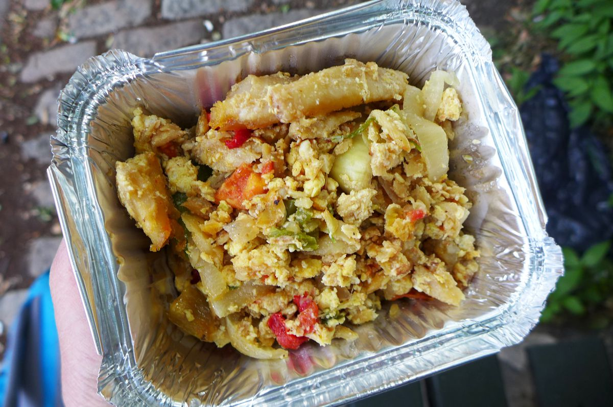 A square metal container with fluffy scrambled cod, eggs, and onions.