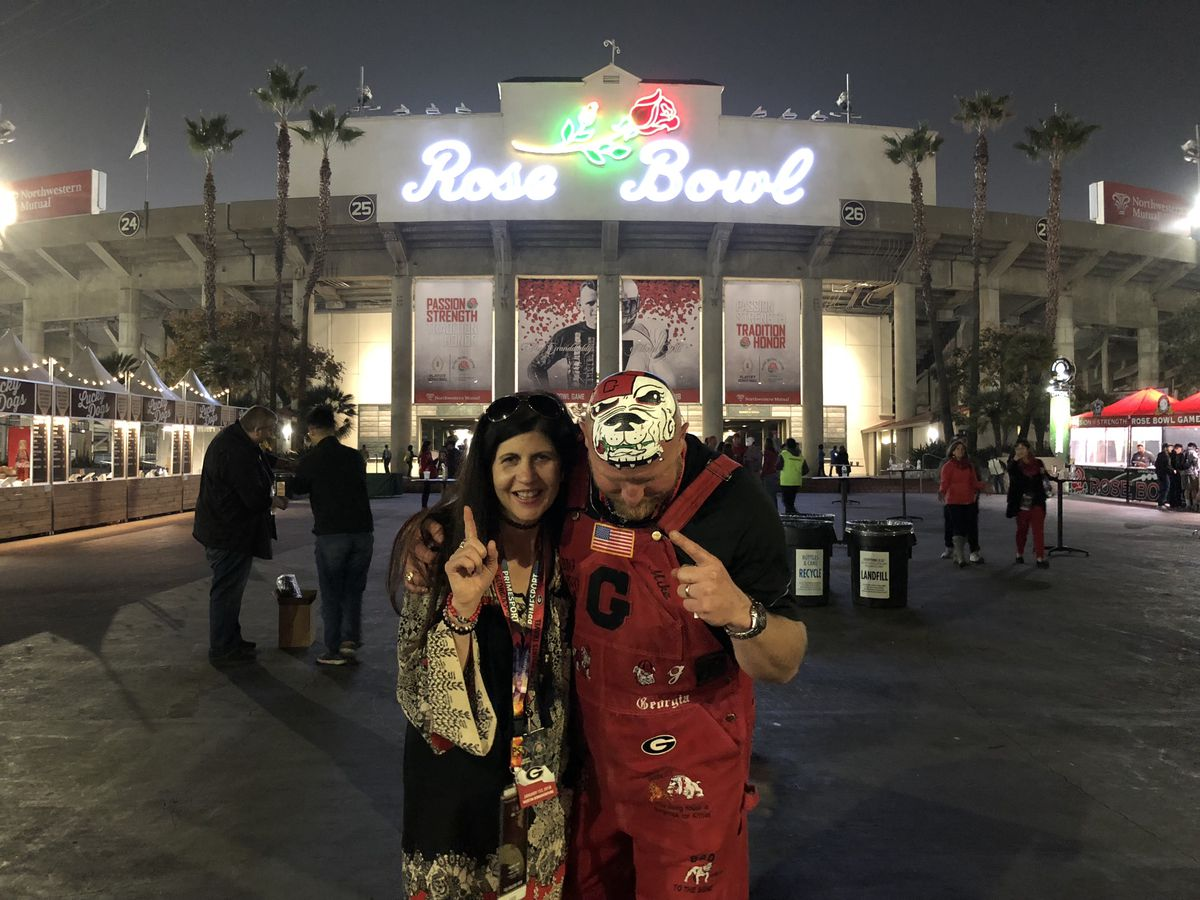 Georgia fan Trent Woods lowers his head, painted with a bulldog on top, and holds up a no. 1 finger in front of the Rose Bowl stadium, where Georgia recently defeated Oklahoma.