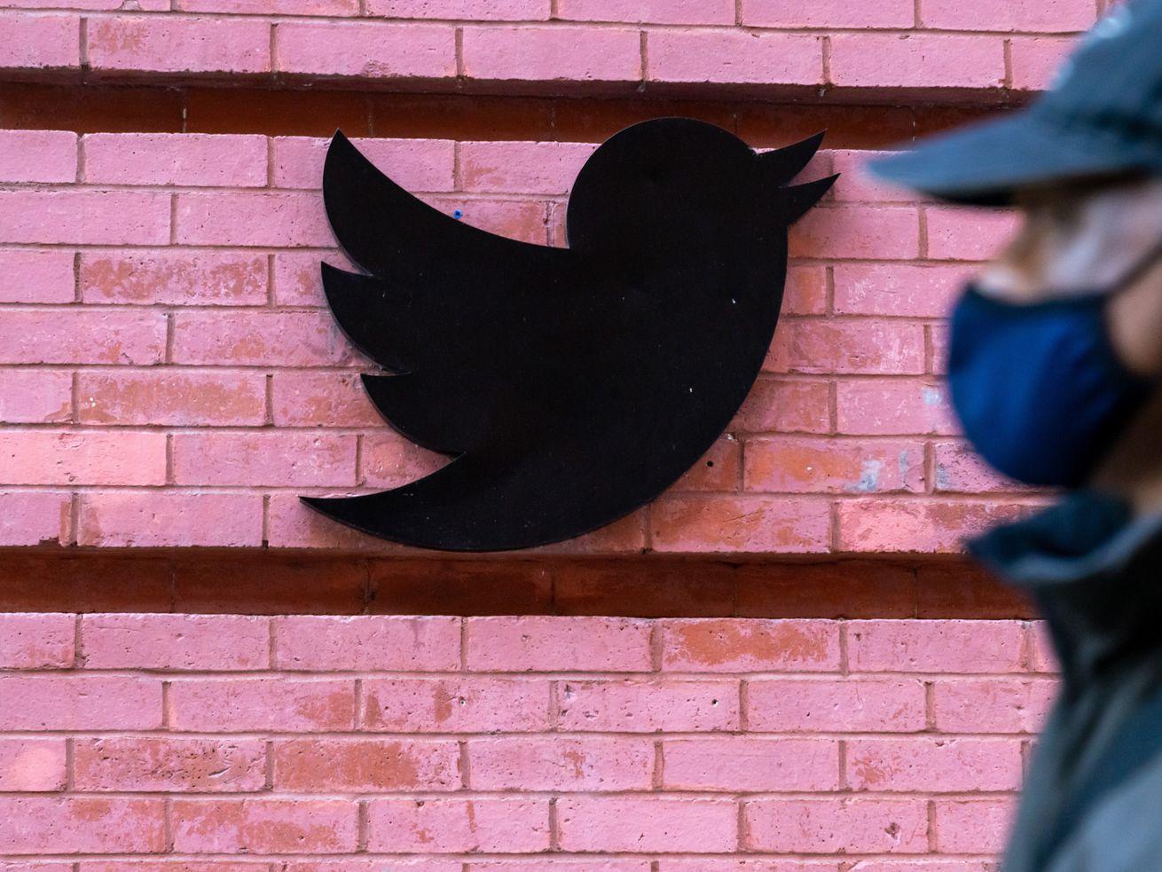 A man wearing a face mask walks past a Twitter logo outside.
