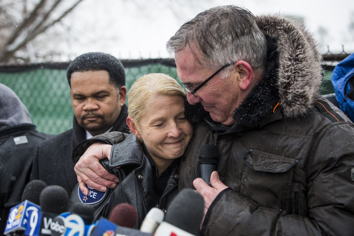 Aurora police Chief Kristen Ziman hugs a chaplain as Mayor Richard Irvin looks on during a prayer vigil after five people were shot to death at the Henry Pratt Company in February. | Ashlee Rezin / Sun-Times